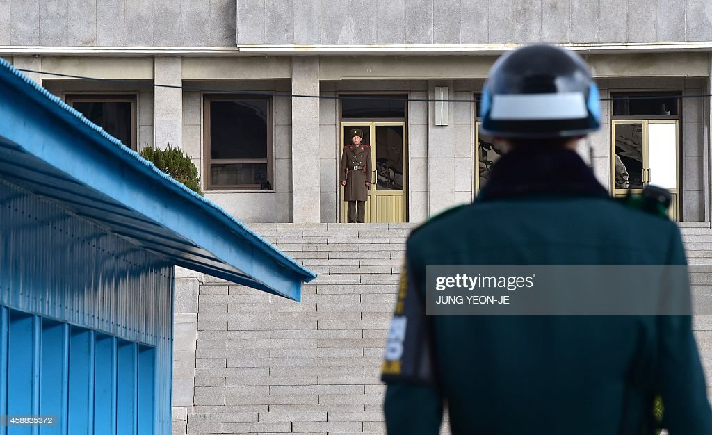 Soldiers from South Korea (R) and North Korea (C back) stand guard on their respective sides at the truce village of Panmunjom in the Demilitarized Zone dividing the two Koreas on November 12, 2014. Under growing pressure at the United Nations over its human rights record, North Korea has accused rival South Korea of its own 'crimes against humanity' over the Sewol ferry tragedy.