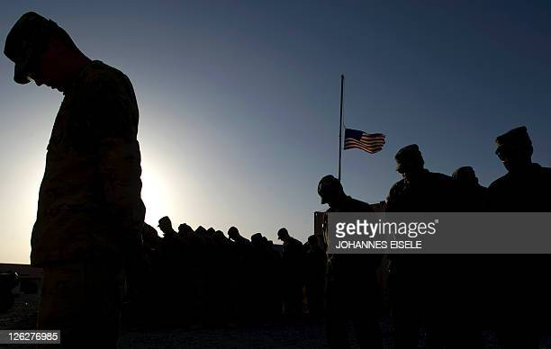 Soldiers from Task Force 366 Bravo Company of the 172 Infantry Brigade bow their heads during a prayer to remember the victims of 9/11 before a...