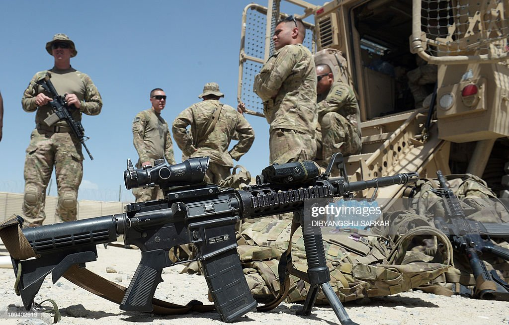 US soldiers from the 10th Mountain Division with their M4 Carbine Rifles relax alongside the Maxxpro Mine Resistant Ambush Protected vechiles prior...