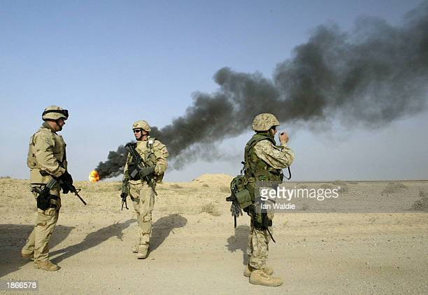 S soldiers from the 1st Marine Expeditionary Force stand guard at a burning oil well at the Rumayla oil fields March 23 2003 in Iraq Several oil...