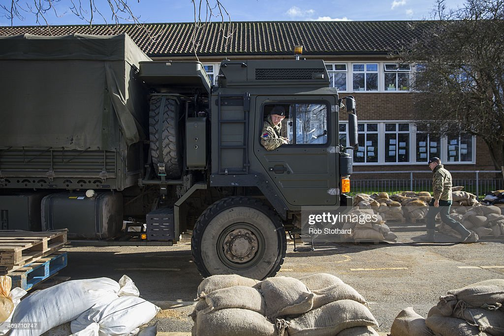 Soldiers from the 1st Regiment Royal Horse Artillery collect sandbags filled by volunteers at The Magna Carter school on February 16 2014 in Staines, England. Housing near the river Thames has suffered a week of flooding after the river burst its banks on February 10, 2014.