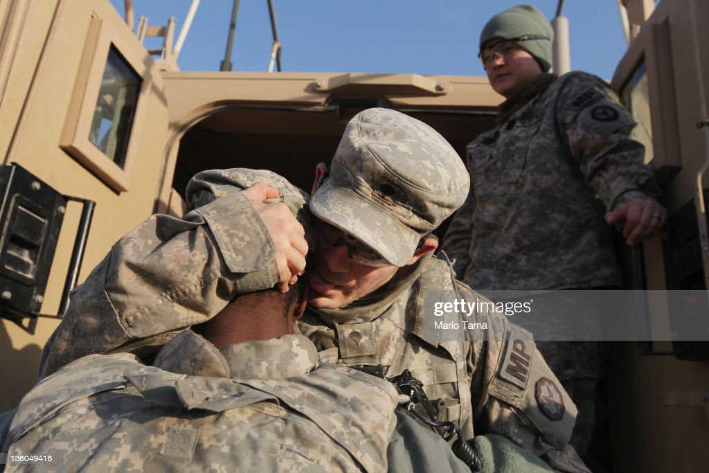 Soldiers from the 3rd Brigade, 1st Cavalry Division hug while preparing to depart in the last convoy from Iraq at Camp Adder, now known as Imam Ali Base, on December 17, 2011 near Nasiriyah, Iraq. Around 500 troops from the 3rd Brigade, 1st Cavalry Division ended their presence on Camp Adder, the last remaining American base, and departed in the final American military convoy out of Iraq, arriving into Kuwait in the early morning hours of December 18, 2011. All U.S. troops were scheduled to have departed Iraq by December 31st, 2011. At least 4,485 U.S. military personnel died in service in Iraq. According to the Iraq Body Count, more than 100,000 Iraqi civilians have died from war-related violence.