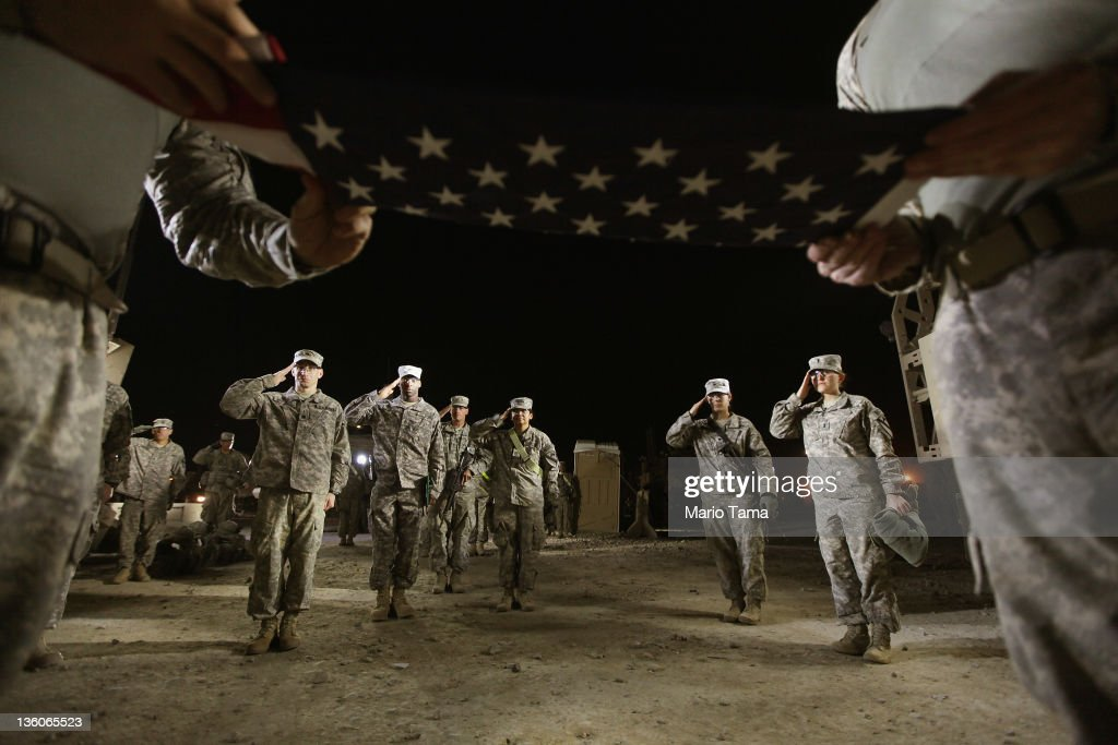 Soldiers from the 3rd Brigade, 1st Cavalry Division salute during a re-enlistment ceremony for Staff Sergeant Brant Smith, from Dothan, Alabama, while preparing to depart in the last convoy from Iraq at Camp Adder, now known as Imam Ali Base, on December 17, 2011 near Nasiriyah, Iraq. Smith re-enlisted for three years of service at the ceremony which he wanted to hold at the staging area for the last convoy. Around 500 troops from the 3rd Brigade, 1st Cavalry Division ended their presence on Camp Adder, the last remaining American base, and departed in the final American military convoy out of Iraq, arriving into Kuwait in the early morning hours of December 18, 2011. All U.S. troops were scheduled to have departed Iraq by December 31st, 2011. At least 4,485 U.S. military personnel died in service in Iraq. According to the Iraq Body Count, more than 100,000 Iraqi civilians have died from war-related violence.