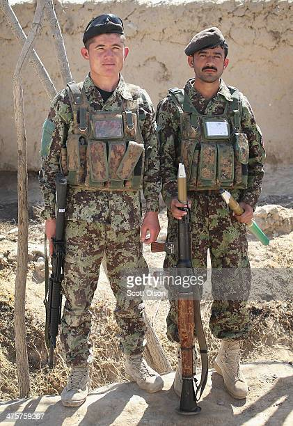 Soldiers from the Afghan National Army pause during a joint patrol with the US Army's 4th squadron 2d Cavalry Regiment on March 1 2014 near Kandahar...