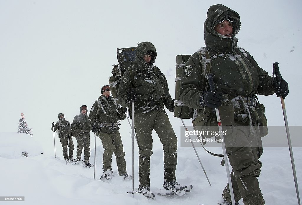 Soldiers from the Austrian armed forces from the 6th Infantry Brigade (6. Jaegerbrigade), of the 2nd Engineer Battalion Salzburg (Pionierbatallion 2), walk with snowshoes during an alpine training winter exercise (above 2000m altitude) during a foggy and snowy day in the Tuxer mountains near Wattens on January 16, 2013. Austrians will decide on Sunday whether to maintain compulsory military service or switch to a professional army in a referendum that has split the small, neutral country. AFP PHOTO / ALEXANDER KLEIN