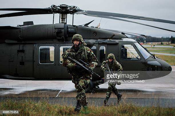 Soldiers from the Defence Forces of Ireland run near a Blackhawk helicopter at Hagshult Airbase part of the Forward Operation Base of the NBG about...