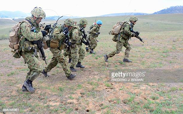 Soldiers from the Japan Ground SelfDefense Force's Western Army Infantry Regiment run to take their position with Exercise Iron Fist 2014 underway...