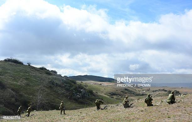 Soldiers from the Japan Ground SelfDefense Force's Western Army Infantry Regiment take their positions from a hilltop with Exercise Iron Fist 2014...