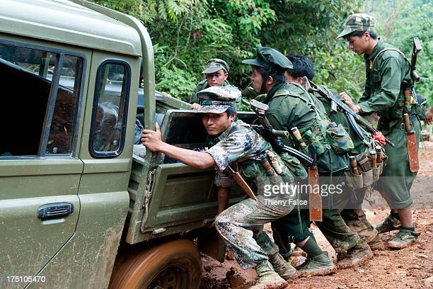 Soldiers from the Kachin Independence Army coming back from the frontline help to move a vehicle stuck in a muddy dirt road With 6000 troops the KIA...