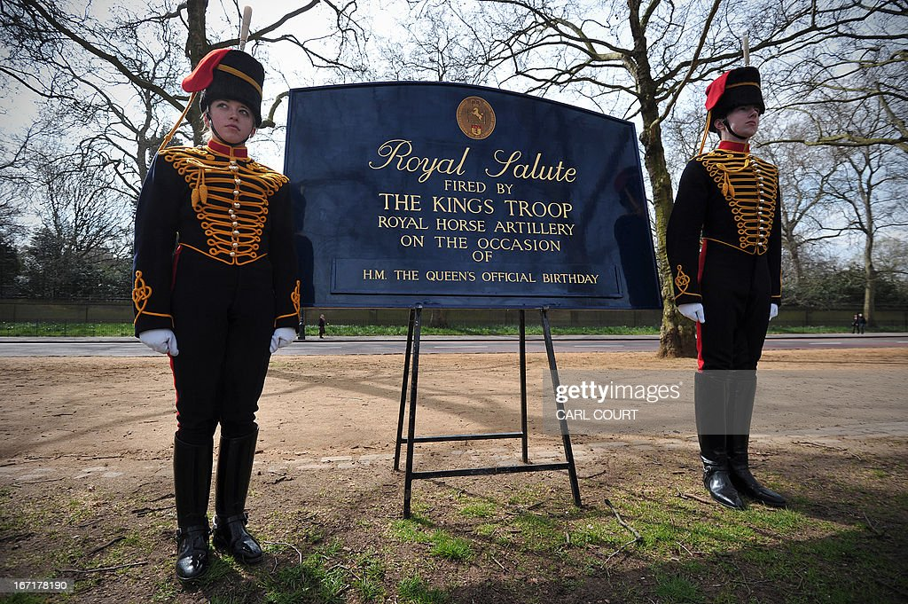 Soldiers from the King's Troop Royal Horse Artillery stand to attention next to a sign announcing the ceremonial 41 Gun Royal Salute to mark the 87th birthday of Britain's Queen Elizabeth II in Green Park in central London on April 22, 2013. PHOTO