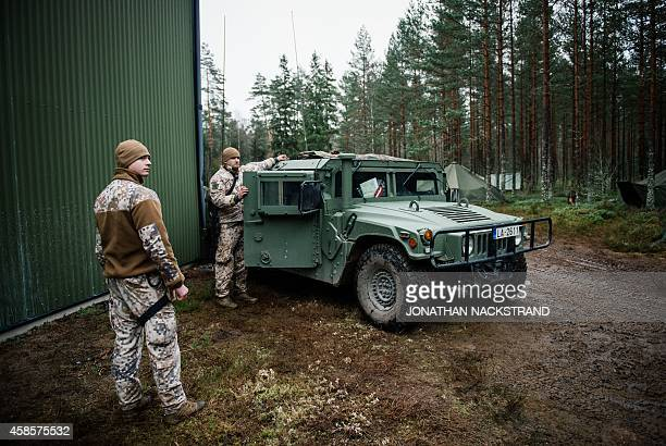 Soldiers from the Latvian National Armed Forces part of the NBG Quick Response Force stand next to an armored Hummer vehicles at Hagshult Airbase...