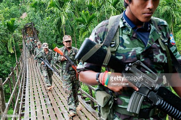 Soldiers from the Mon National Liberation Army are walking on a suspended bridge across a river during a patrol in a resettlement site for former Mon...