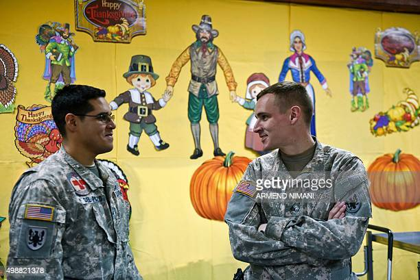 US soldiers from the NATO ledpeacekeeping mission in Kosovo talk during a traditional Thanksgiving meal at the US military base Camp Bondsteel near...