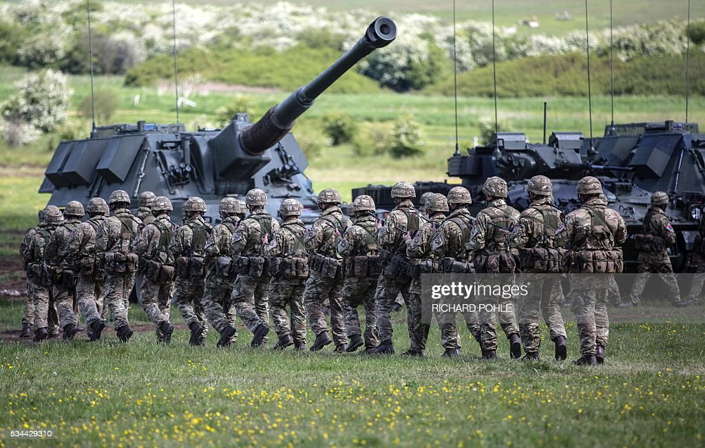Soldiers from the parade in front of military equiptment as Britain's Queen Elizabeth II (unseen) reviews the Royal Regiment of Artillery at Knighton Down, Larkhill on Salisbury plain, southern England on May 26, 2016. 2016 marks the Tercentenary of the formation of the Royal Artillery when, on 26 May 1716, by Royal Warrant of King George 1, two companies of artillery were formed at Woolwich in London, alongside the guns, powder and shot located in the Royal Arsenal. / AFP / RICHARD