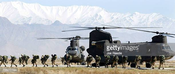 Soldiers from the US Armys 10th Mountain and 101st Airborne Division disembark from their chinook helicopter March 12 2002 after returning to Bagram...