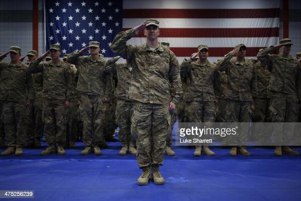 Soldiers from the US Army's 3rd Brigade Combat Team 1st Infantry Division salute during the playing of the Star Spangled Banner during a homecoming...