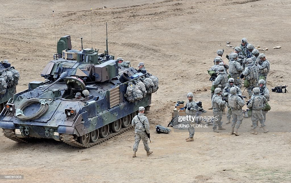 US soldiers gather next to a Bradley armored vehicle at a military training field in the border city of Yeoncheon, northeast of Seoul, on April 11, 2013. The United States has warned North Korea it is skating a 'dangerous line' with an expected missile launch that could start a whole new cycle of escalating tensions in a region already on a hair-trigger.