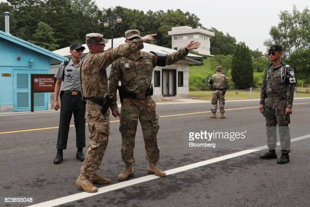 US soldiers gesture towards the southern side of the truce village of Panmunjom in the Demilitarized Zone in Paju South Korea on Thursday July 27...