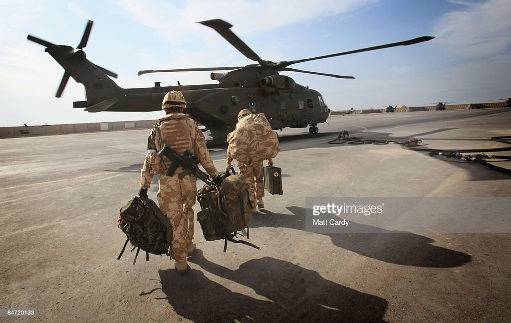 Soldiers get on board a helicopter at the Helicopter Landing Station inside the main British base the Combined Operating Base at Basra Airport on...