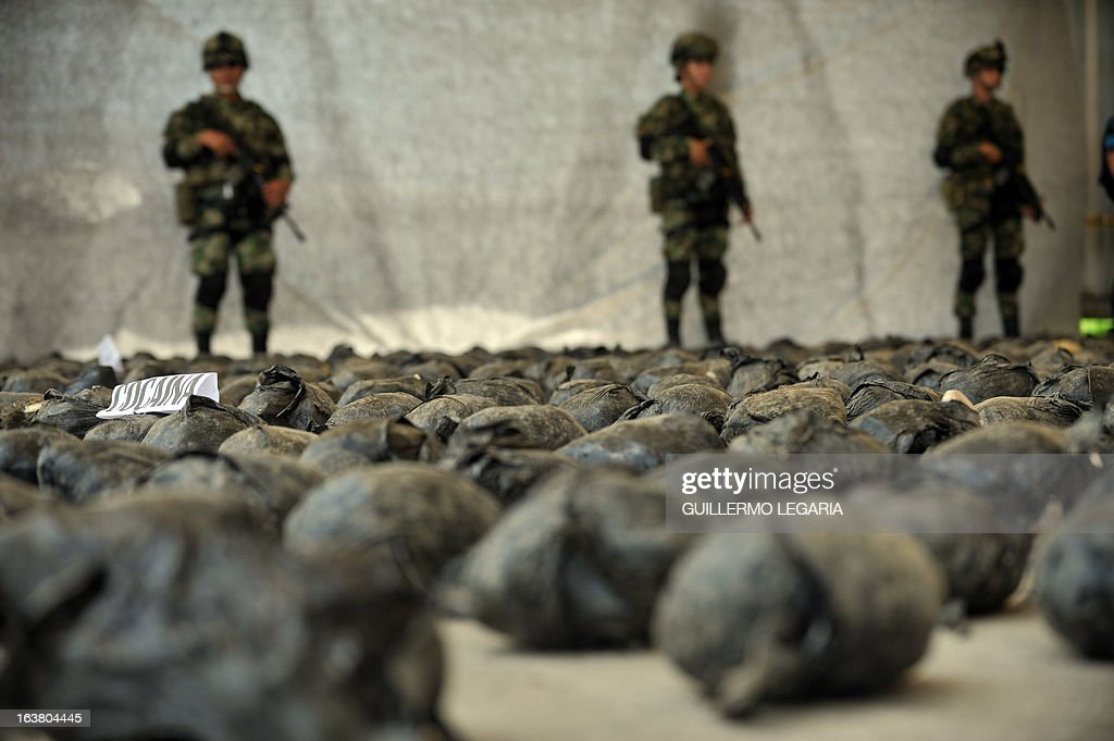 Soldiers guard a shipment of 3,9 tons of cocaine seized in a large clandestine laboratory for the production of the drug, during its presentation to the press on March 16, 2013, at the military air base in Tumaco, Narino department, Colombia. Soldiers from special counternarcotics brigade found and destroyed on 13 March, in the municipality of Timbiqui, Cauca deparment, a huget laboratory to produce cocaine, considered by authorities as the largest collection center for alkaloids processing of the Revolutionary Armed Forces of Colombia (FARC) and from which drug was sent to Central and North America, officials said. AFP PHOTO/Guillermo Legaria