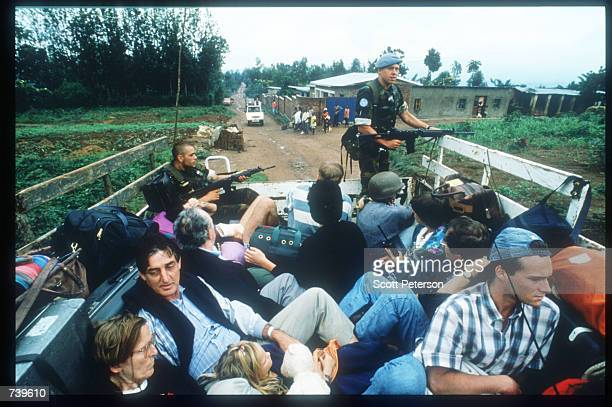 Soldiers guard a truckload of civilians as they evacuate April 11 1994 from Kigali Rwanda The majority of French and Belgian nationals living in...