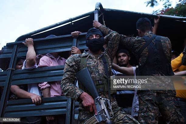 Soldiers guard a vehicle that is used to transport people in San Salvador on July 29 during the third day of a transport strike in El Salvador over...