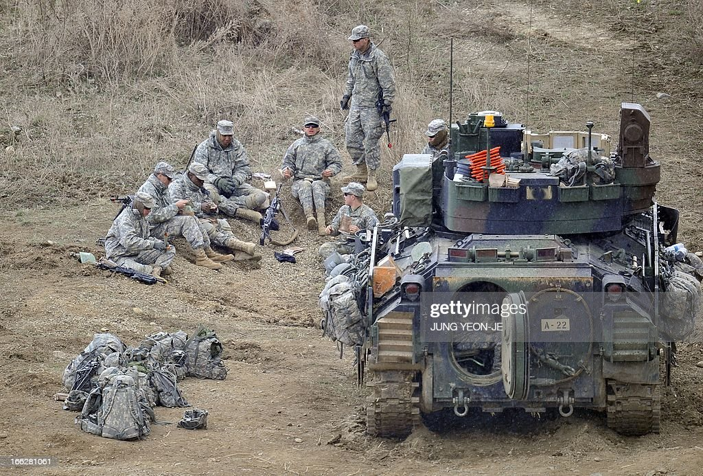US soldiers have a lunch next to a Bradley armored vehicle at a military training field in the border city of Yeoncheon, northeast of Seoul, on April 11, 2013. The United States has warned North Korea it is skating a 'dangerous line' with an expected missile launch that could start a whole new cycle of escalating tensions in a region already on a hair-trigger.