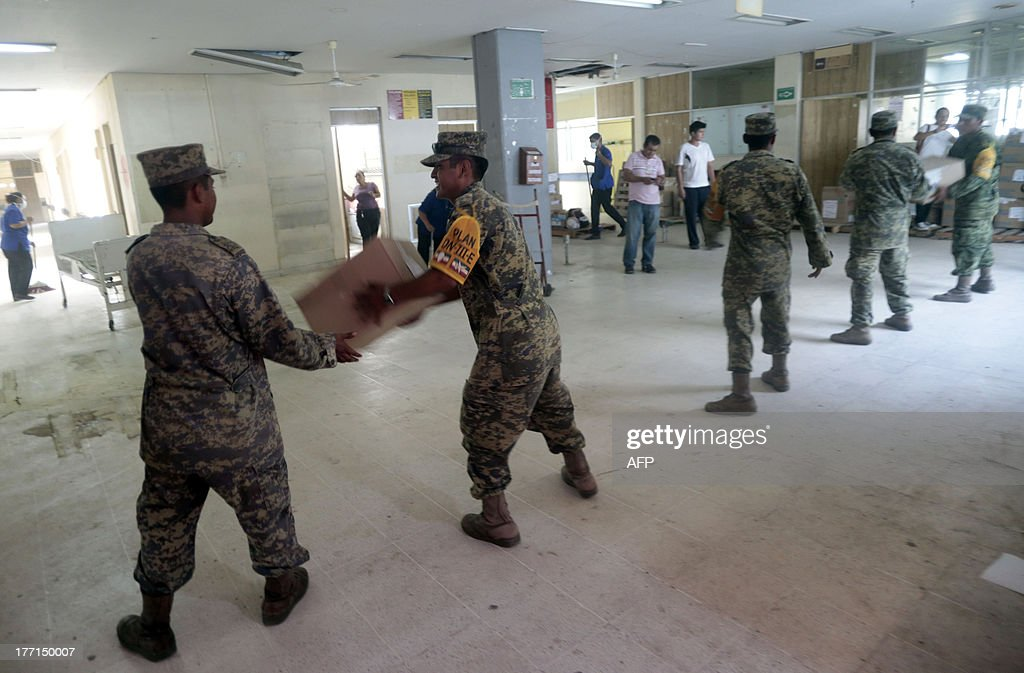 Soldiers help in the evacuation of the Alarcon Hospital in Acapulco after a 5.62-magnitude aftershock which was reported minutes after a 6.0 magnitude earthquake shook Mexico City on August 21, 2013. A strong 6.0 magnitude earthquake and an aftershock rattled Mexico on Wednesday, causing evacuations of buildings in the capital and hotels in the Pacific resort of Acapulco. The quake's epicenter has been located 17 km west of the town of San Marcos in the southern state of Guerrero, the National Seismology Center said. A 5.62-magnitude aftershock was reported 20 minutes later 14 km northeast of Acapulco, where rocks from a hill rolled into a street and some hotel facades showed cracks while tourists poured into the streets. AFP PHOTO / Pedro PARDO