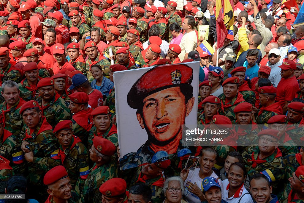 Soldiers holds a portrait of late Venezuelan President Hugo Chavez during a ceremony to commemorate the 24th anniversary of Chavez's military coup...
