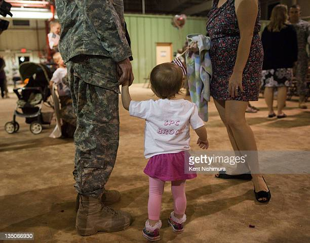 A soldiers holdst the hands of a child as the 25th Infantry Division are greeted by family friends and loved ones at the Second 25th Infantry...