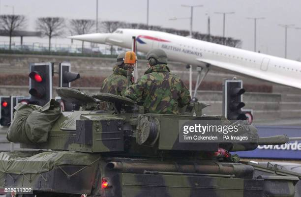 Soldiers in an armoured car stand guard in front of a model of a Britsh Airways Concorde near the entrance to London's Heathrow airport * Scotland...