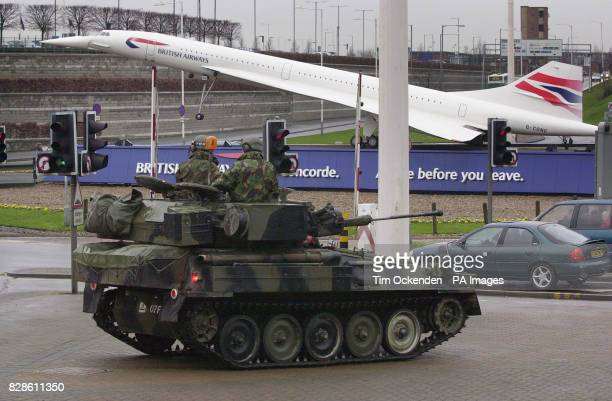 Soldiers in an armoured car stand guard in front of a model of a BritIsh Airways Concorde near the entrance to London's Heathrow airport * Scotland...