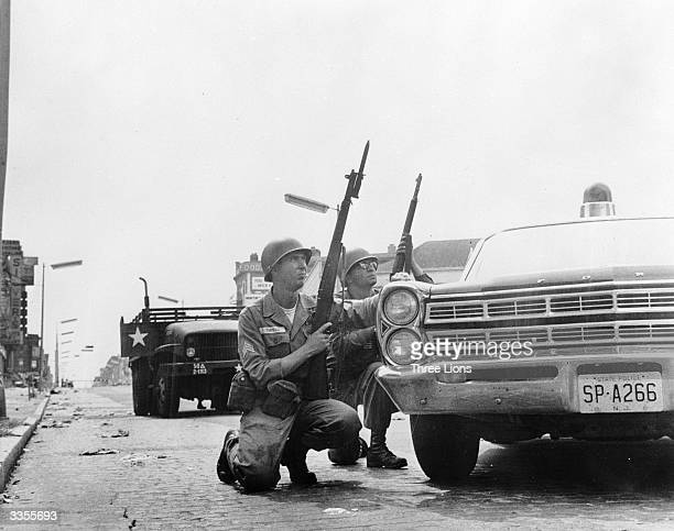 Soldiers in Newark New Jersey taking cover behind police cars while attempting to locate a sniper firing from a window opposite during race riots in...