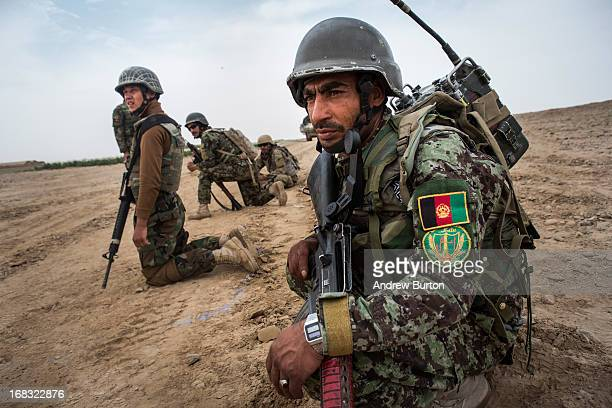 Soldiers in the Afghan National Army's 6th Kandak 3rd company monitor the landscape after a US vehicle hit an improvised explosive device during a...