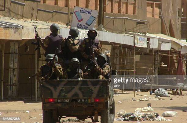 Soldiers in the back of a pickup truck drive down a street during a demonstration in Gao on July 12 2016 against the 'injustices' in the...