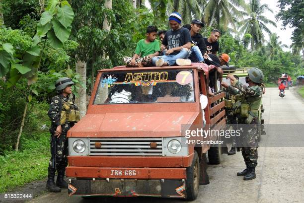 Soldiers inspect a passenger vehicle at a checkpoint in Jolo Sulu on the southern Philippine Island of Mindanao on July 16 2017 Three inmates were...