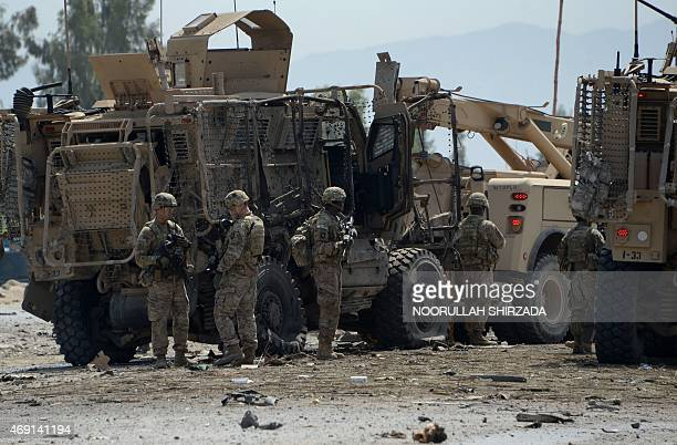 US soldiers inspect the scene of a suicide bomb attack near the airport in the Afghan city of Jalalabad on April 10 2015 A suicide car bomb targeted...