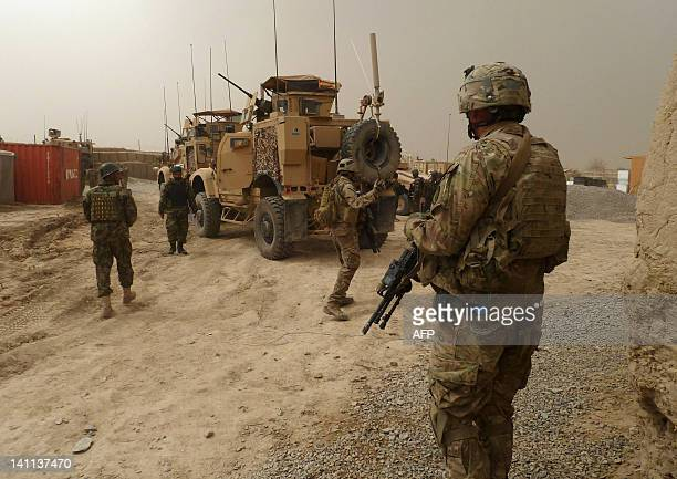 US soldiers keep watch at the entrance of a military base near Alkozai village following the shooting of Afghan civilians allegedly committed by a...