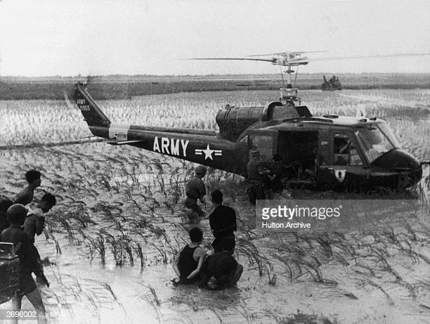 US soldiers lead captured Viet Cong guerillas onto an army helicopter which sits in a flooded rice field during the Vietnam War The prisoners sit...