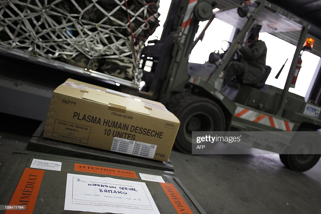 Soldiers load material including plasma (foreground) in a British army Boeing C-17 cargo aircraft arriving from British Brize Norton base en route to Bamako, on January 13, 2013 at the Evreux military Base. Britain supports France's decision to send troops to support an offensive by Mali government forces against Islamist rebels.