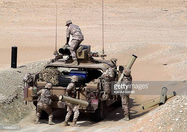 UAE soldiers load their military vehicle with rockets during manoeuvres with the French army in the desert of Abu Dhabi May 2 2012 AFP PHOTO/KARIM...