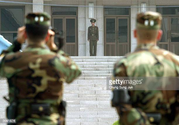 S soldiers look at a North Korean soldier at the border village of Panmunjom June 18 2003 north of Seoul South Korea North Korea vowed to strengthen...