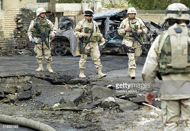 US soldiers look at the crater caused by a car bomb that detonated close to the villa housing the Dubaibased AlArabiya satellite television station...