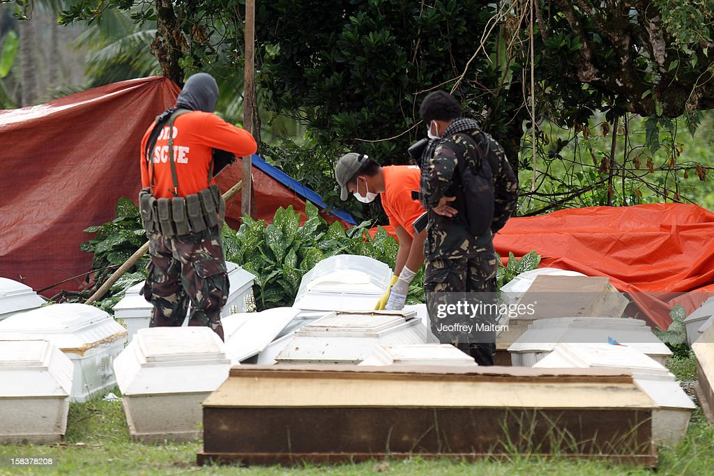 Soldiers look over coffins containing the dead December 14, 2012 in the devastated town of New Bataan, Compostela Valley province, the Philippines. More than 900 people were killed and nearly a thousand remain missing after Typhoon Bopha, the strongest storm to hit the Philippines this year, pounded the region.