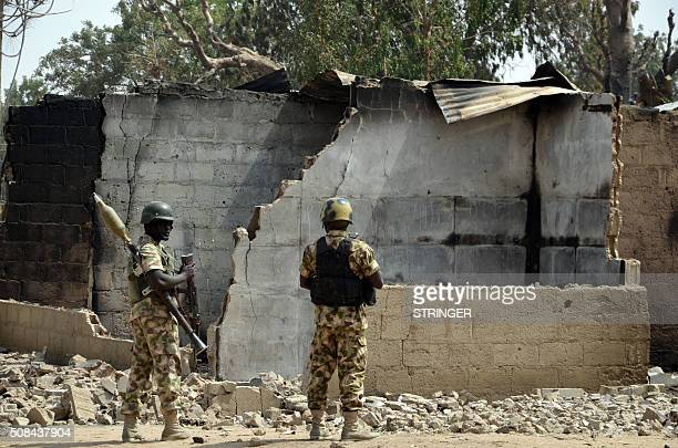 Soldiers looks at burnt house on February 4 2016 during a visit to the village of Dalori village some 12 kilometres from Borno state capital...