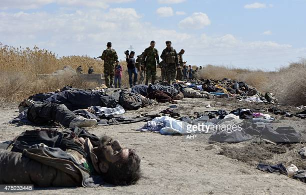 Soldiers loyal to Syrian President Bashar alAssad stand next to corpses of dozens of rebel fighters in the area of Oteiba east of the Syrian capital...