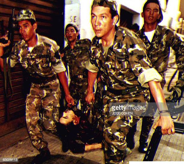 Soldiers loyal to Venezuelan President Carlos Andres Perez carry a comrade's body 27 November after he was killed by rebels attempting to overthrow...