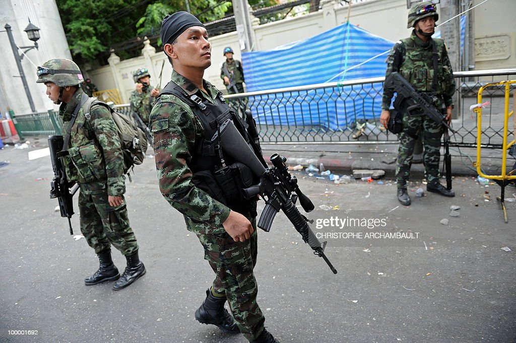 Soldiers make their way into a dismantled anti-government protest zone after gunshots were heard near a Buddhist temple, in downtown Bangkok on May 20, 2010. Gunshots rang out near a Buddhist temple in the heart of an anti-government protest zone in Bangkok, and soldiers were advancing on foot along an elevated train track, an AFP photographer saw. Thai security forces stormed the 'Red Shirts' protest camp on May 19 in a bloody assault that forced the surrender of the movement's leaders who asked their supporters to disperse. AFP PHOTO/Christophe ARCHAMBAULT