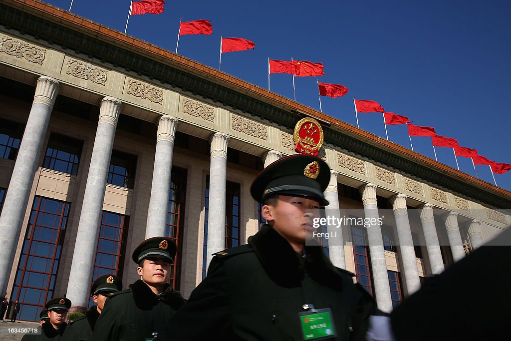 Soldiers march outside the Great Hall of the People where a session of National People's Congress is held on March 10, 2013 in Beijing, China. The State Council, China's cabinet, will begin its seventh restructuring attempt in the past three decades to roll back red tape and reduce administrative intervention. Several departments under the State Council will be reorganized according to a plan on the institutional restructuring and functional transformation of the State Council, which was submitted to the plenary session of the National People's Congress Sunday.