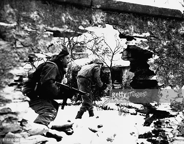 Soldiers move stealthily through the snow during the Battle of the Bulge